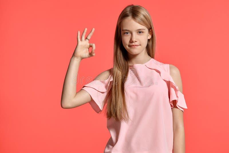 Studiostående av en blond tonåring för härlig flicka i en rosig t-skjorta som poserar på rosa bakgrund royaltyfri foto