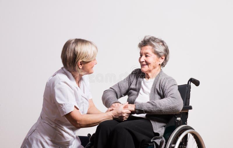 Studiostående av en hög sjuksköterska och en äldre kvinna i rullstol royaltyfri bild