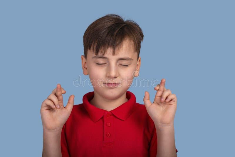 Studiostående av a av en pojke med stängda ögon som föreslår en lust och visar händer med korsade fingrar på blå bakgrund in royaltyfria foton
