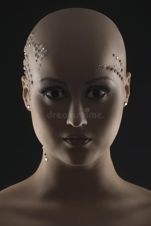Studiostående av en skallig flicka på svart bakgrund arkivbilder
