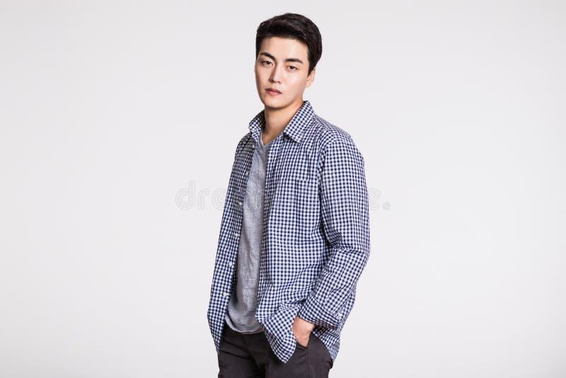 Studiostående av en stilig ung man som säkert poserar mot en grå bakgrund royaltyfri foto