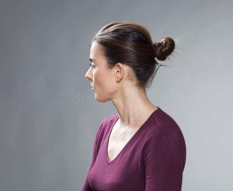 Studiostående av en tänkande 30-talkvinna, profilsikt royaltyfri fotografi