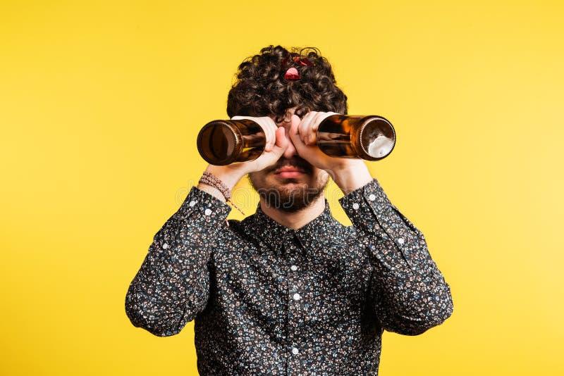 Studiostående av flaskor för ett innehav för ung man på en gul bakgrund arkivbild