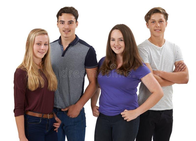 Studiostående av gruppen av tonårs- vänner som står mot vit bakgrund royaltyfria bilder
