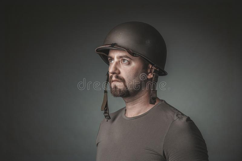 Studiostående av mannen med den militära hjälmen som bort ser arkivbild