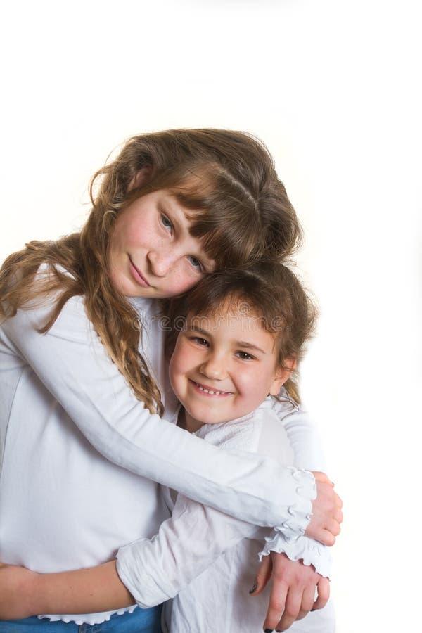 Studiostående av två unga lyckliga le flickor, systrar, över royaltyfri fotografi