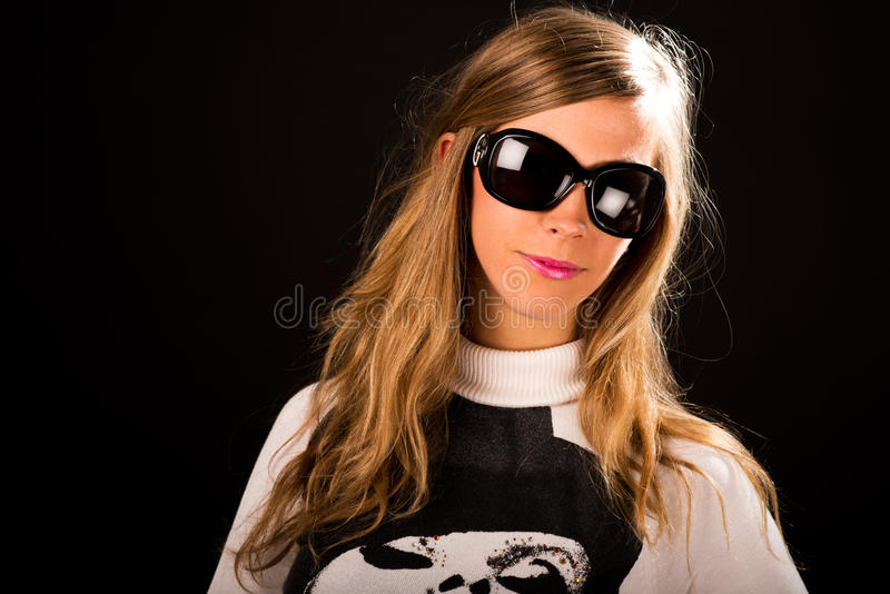Studiostående för ung kvinna på svart bakgrund med solglasögon arkivfoto