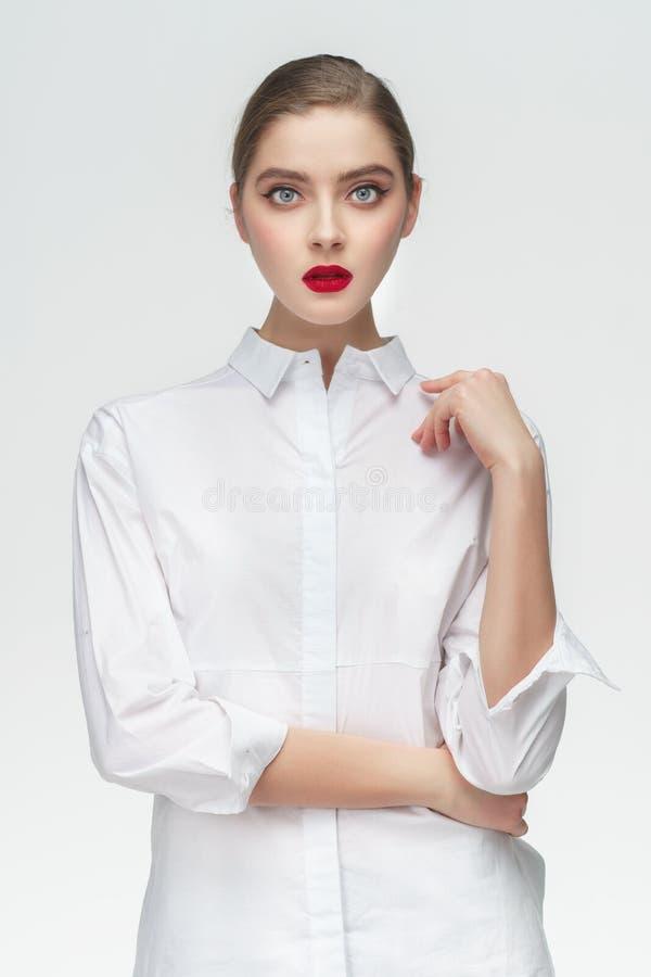 Studioståenden av affärsflickan i den vita skjortan på grå färger isolerade bakgrund Begrepp: en allvarlig flickachef eller stude royaltyfria foton