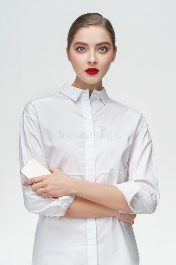 Studioståenden av affärsflickan i den vita skjortan på grå färger isolerade bakgrund Begrepp: en allvarlig flickachef eller stude arkivfoto