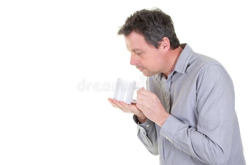 Studioståenden av den stiliga mannen som rymmer te, rånar eller koppen kaffe royaltyfri bild