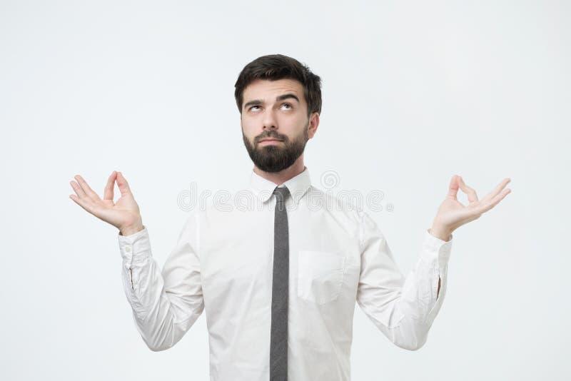 Studioståenden av den unga stiliga mannen i den vita skjortan, i meditation poserar och att försöka att koppla av royaltyfria foton