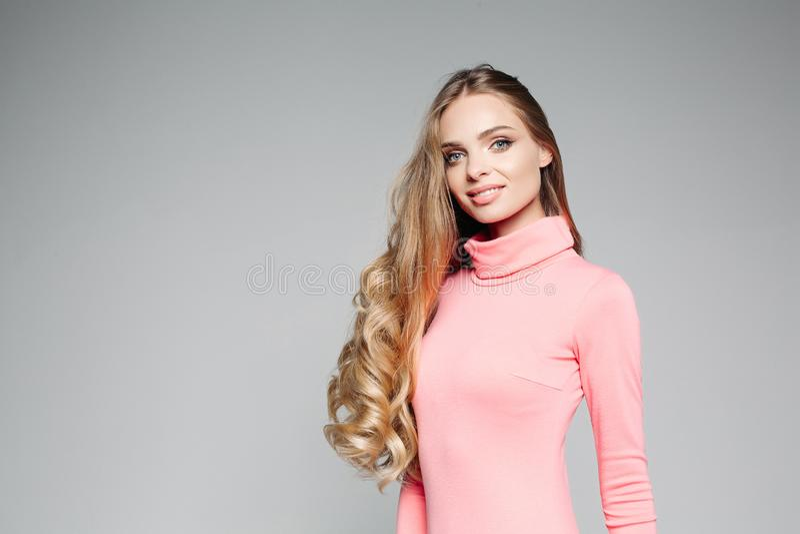 Studioståenden av en härlig affärskvinna som är blond med blåa ögon med långt hår, bär en elegant rosa färgklänning och rymmer royaltyfria bilder