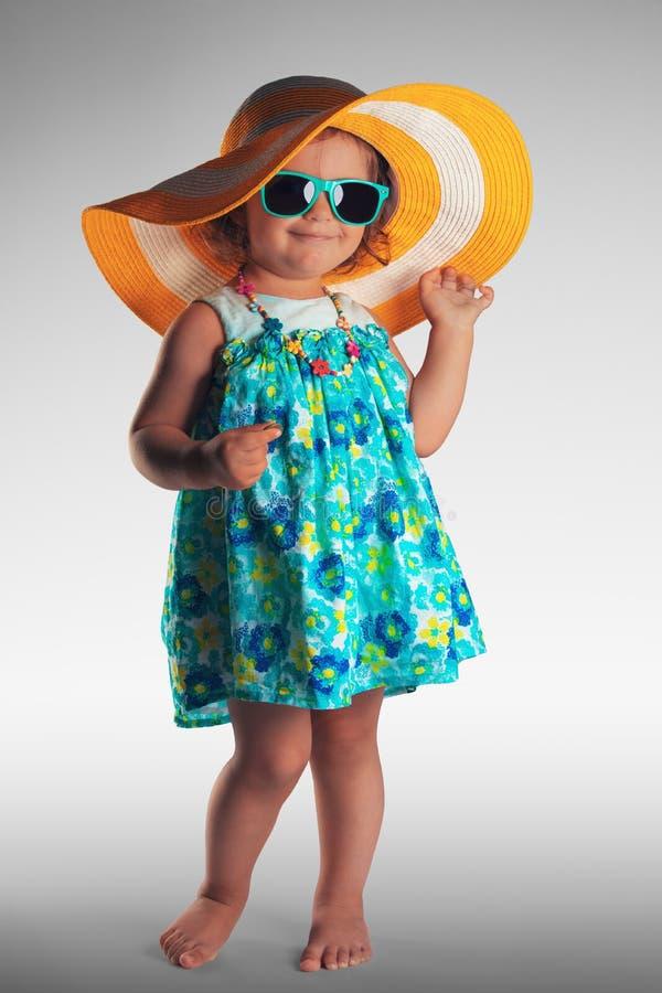 Studioståenden av gulligt behandla som ett barn flickan med hatten och solglasögon, summe arkivbild