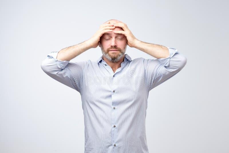 Studioståenden av rubbningen oroade den ledsna, deprimerade trötta mannen med en huvudvärk och den mycket stressade framsidan royaltyfria bilder