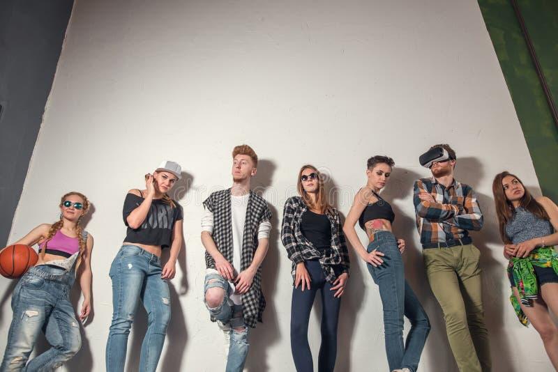 Studioståenden av sju barn danar attraktiva le caucasian kvinnor, och klädd jeans för män grupperar vänner tillsammans fotografering för bildbyråer