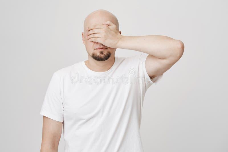 Studioståenden av skallig skäggig caucasian grabbbeläggning för stillhet synar med handen, den bärande vita t-skjortan och anseen royaltyfri fotografi