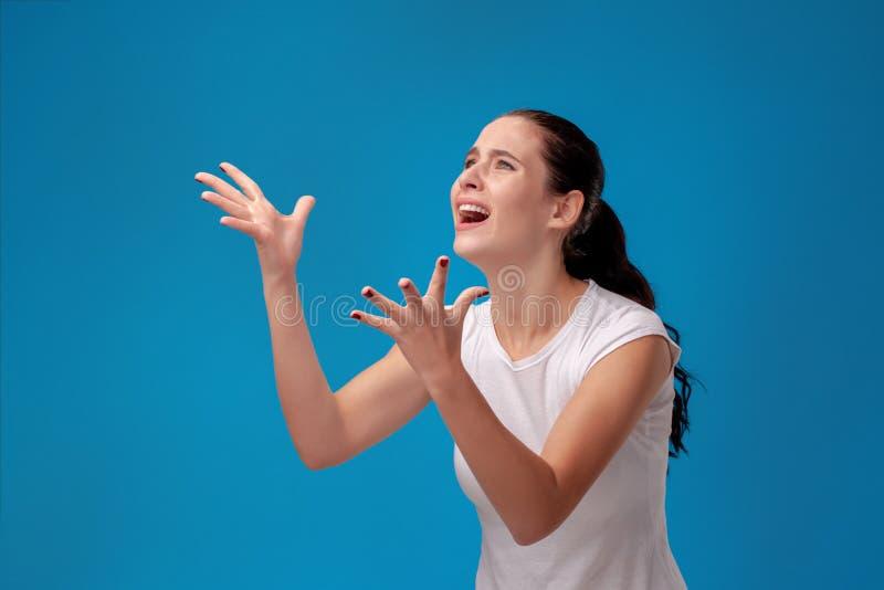 Studiost?ende av en ung h?rlig kvinna i en vit t-skjorta mot en bl? v?ggbakgrund ?rliga sinnesr?relser f?r folk royaltyfria foton
