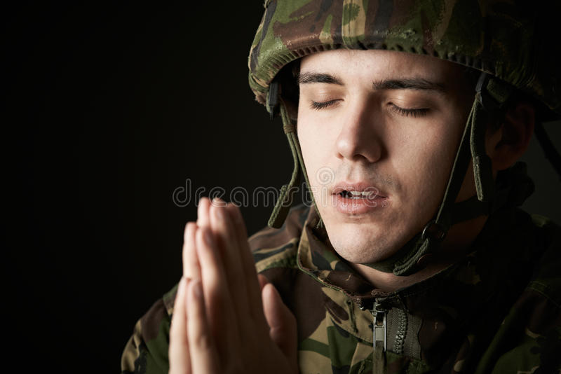 Studiostående av soldaten In Uniform Praying arkivbild