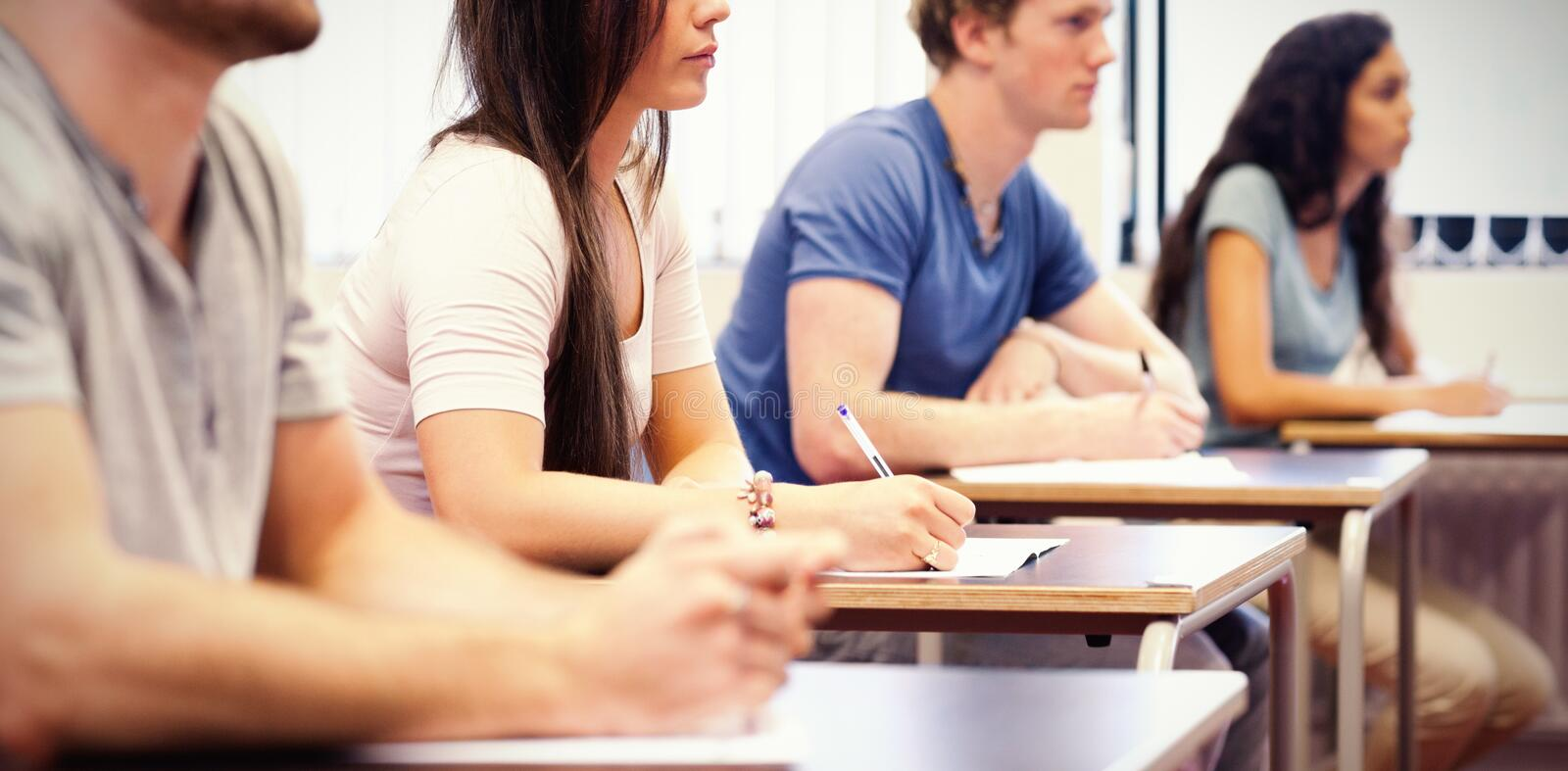 Studious young adults listening in classroom royalty free stock photography