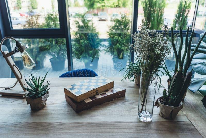 Studiowerkplaats met schaakraad, artistieke het werkhulpmiddelen en groene installaties stock foto's