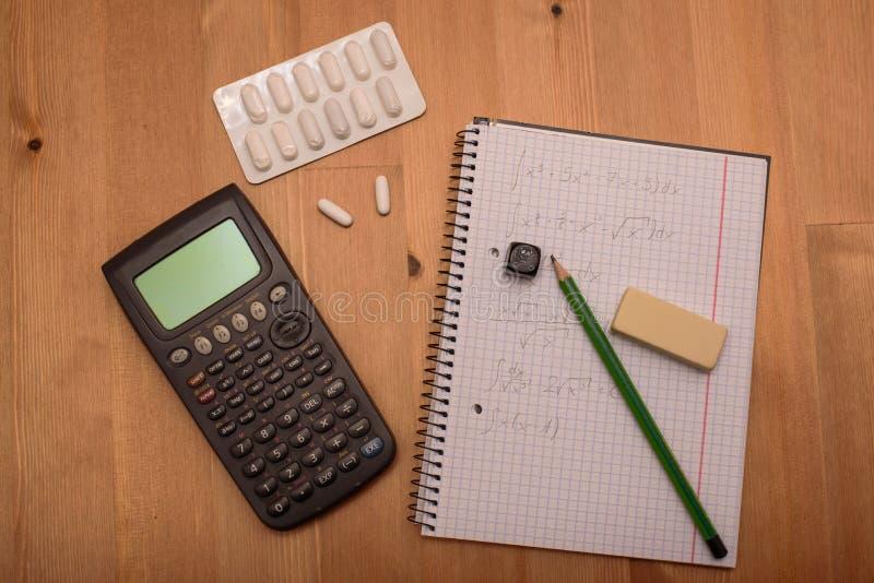 Studiuje miejsce z kalkulatorem i środkami przeciwbólowymi w tle zdjęcia stock