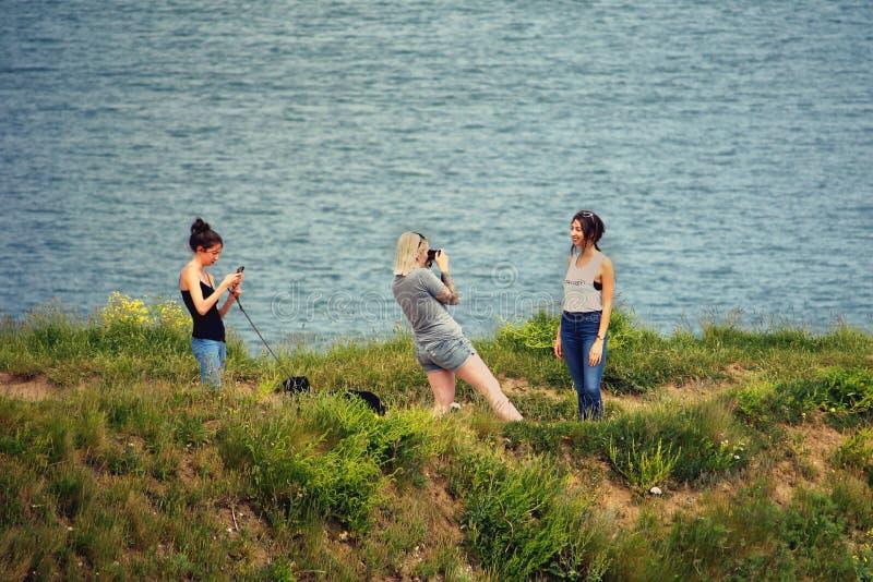 Studland,多西特,英国- 2018年6月04日:拍手机照片彼此的三个少妇在沿海陆岬 库存图片