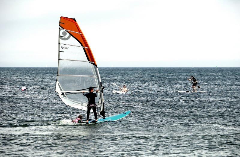 Studland, Dorset, Angleterre - 1er juin 2018 : Vacanciers nageant, faisant de la planche à voile, kayaking et embarquement de pal photo libre de droits