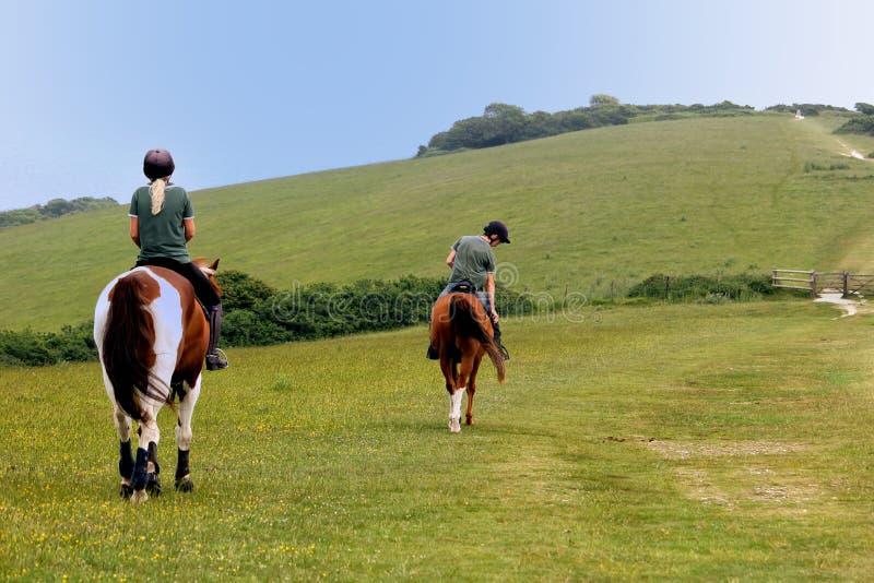 Studland, Dorset, Reino Unido - 4 de junho de 2018: Duas mulheres a cavalo, andando ao longo de um trajeto da costa em um promont imagens de stock