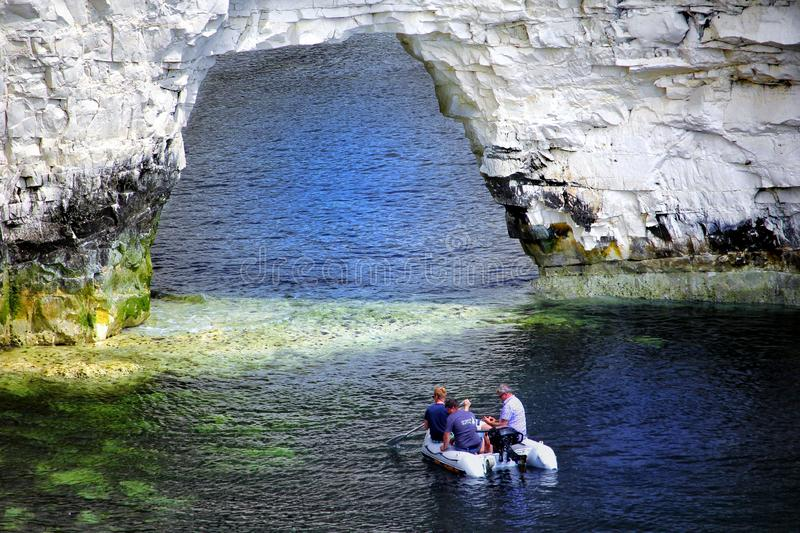 Studland, Dorset, UK - June 04 2018: Three men in a small rubber dinghy, about to go through a chalk cliff arch on the sea coastbl. Studland, Dorset, UK - June royalty free stock image