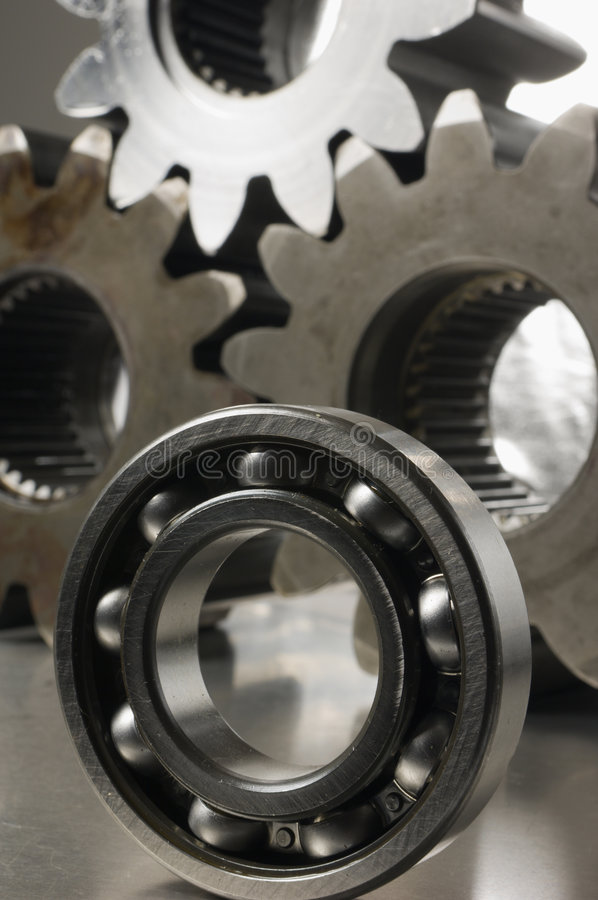 Study of ball-bearing against gears backdrop royalty free stock photography