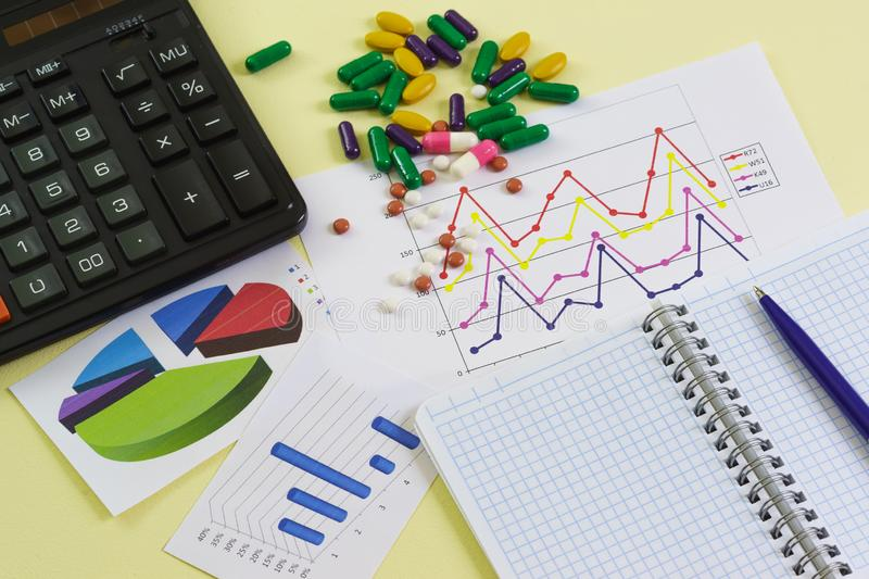 The study of the effectiveness of drugs. Calculator, colorful graphics, Notepad and tablets. On the table stock photography