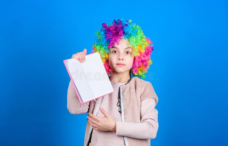 Study hard. Ridiculous story. Reading funny book. Literature club. Jokes book concept. Kid colorful curly wig artificial. Hair clown style hold book. Reading stock image