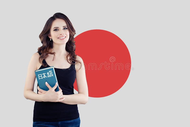 Study Japanese language. Pretty brunette girl student with Japan flag royalty free stock photo