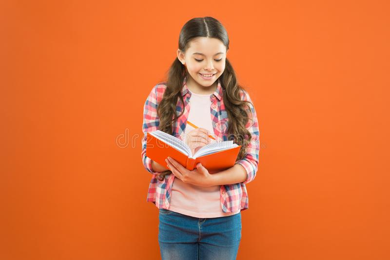 Study language. Making notes. Child doing homework writing in workbook. Girl hold book and pen. Girl cute write down. Idea notes. Notes to remember. Write essay stock image