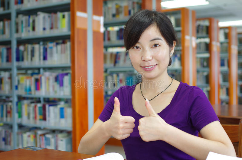 Study in a library. Young girl gestures thumbs up in a library stock image