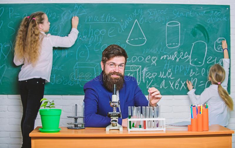 Study for a test. School teacher and study group. Little children and science teacher having study session. Carrying out stock photography