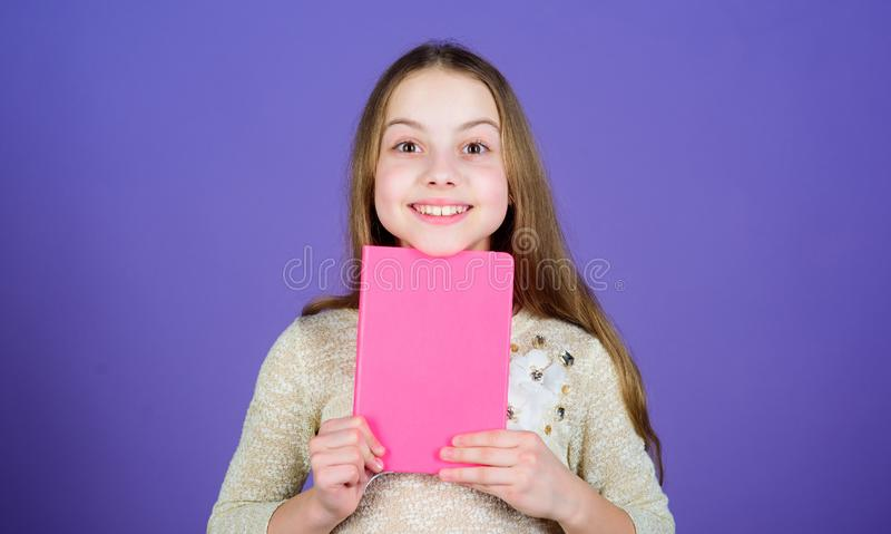 Study what you love and intern in what you want to do. Adorable little girl holding study book with rosy cover. Cute royalty free stock images