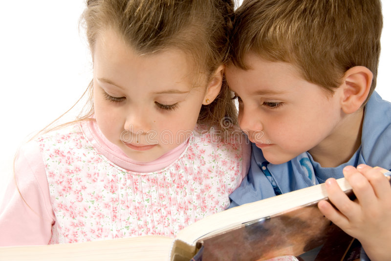 Studying. Brother and sister reading a big book stock images