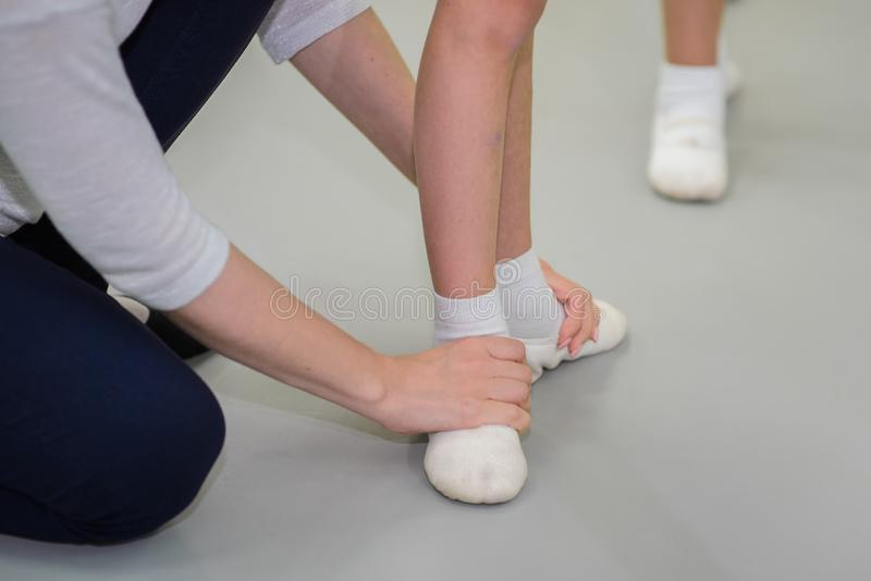 Studying ballet. Foot basic first position training. Teacher corrects ballerinas pose, closeup view of hands and feets. royalty free stock photos