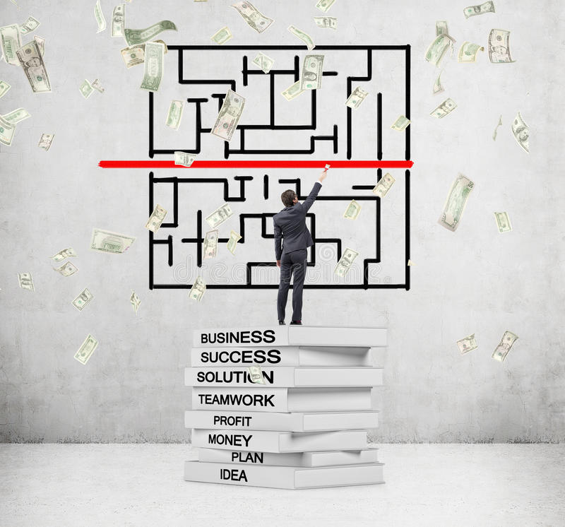 Studying business. Man standing on pile of books with key business words written on backs and painting red line, dollars falling from above. Concrete background royalty free stock photos