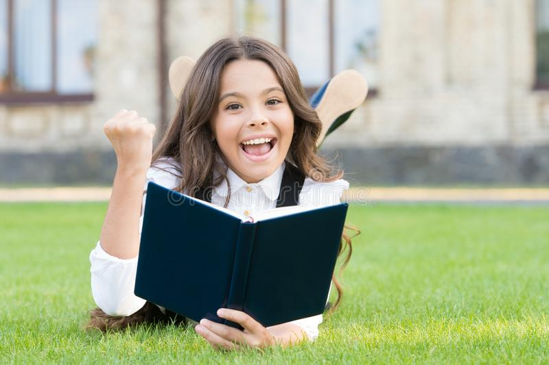 Studying concept. Schoolgirl school uniform laying on lawn with favorite book. Extracurricular reading. Cute small child. Reading book outdoors. Basic education royalty free stock images