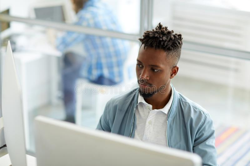 Studying data. Young African-american businessman sitting in front of two computer monitors and analyzing data stock photo