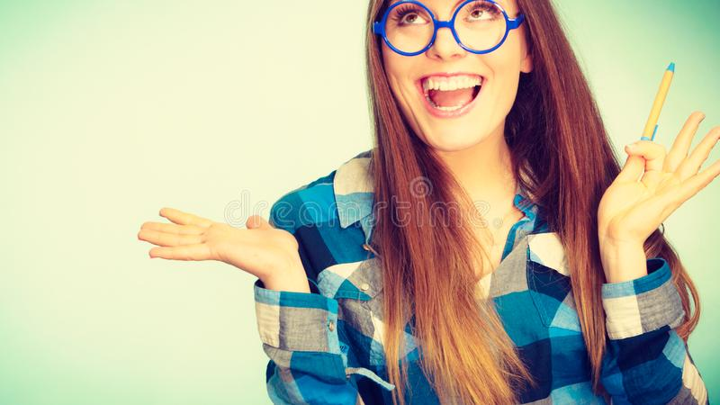 Happy nerdy woman in glasses holding pen stock photos