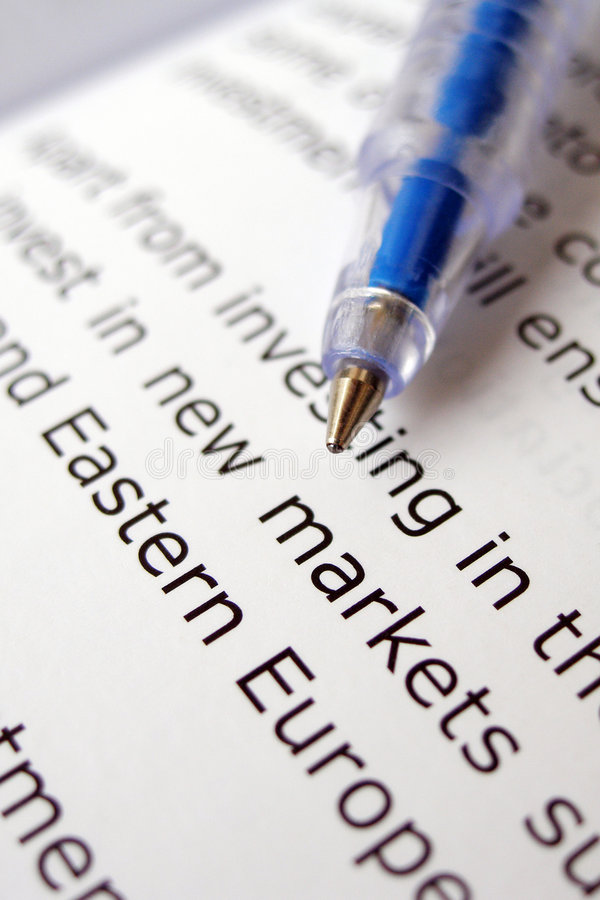 Studying about new markets. An image of a new ball point pen poised over a page of an open book, pointing to words new markets. Shallow dof to emphsize the two royalty free stock photography