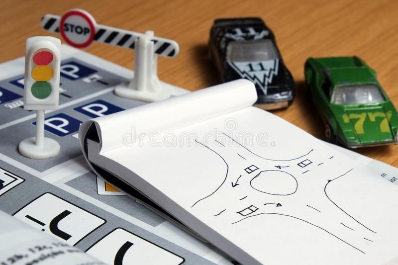 Studying and preparing for driving test. Notepad, book of traffic rules, toy cars, traffic lights and stop sign on a desk table. Studying and preparing for royalty free stock photography