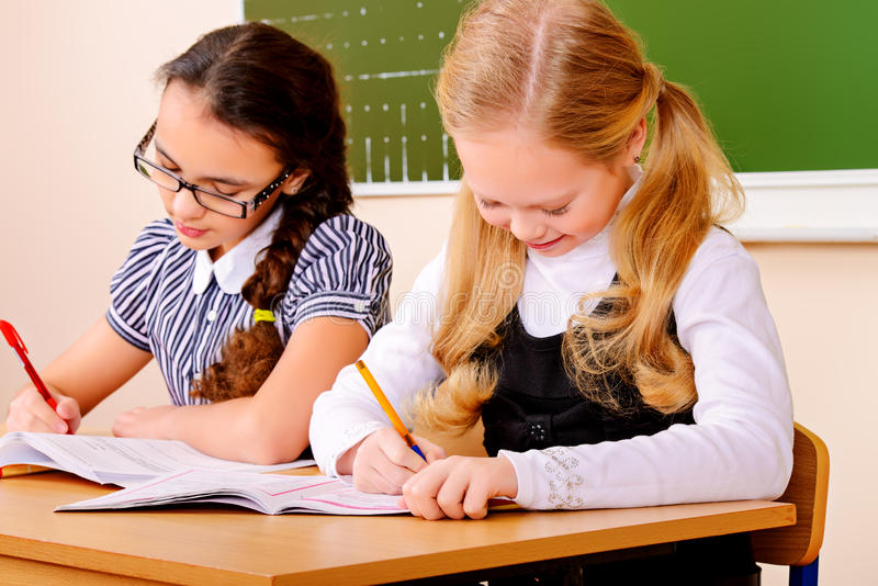 Studying. Schoolgirls sit at their desk during a lesson. Education royalty free stock photography