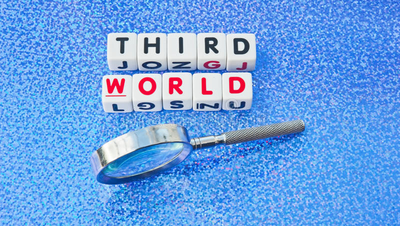 Studying the third world. Text ' third world' in uppercase letters inscribed on small white cubes with hand magnifier beside to emphasize study, blue background stock images