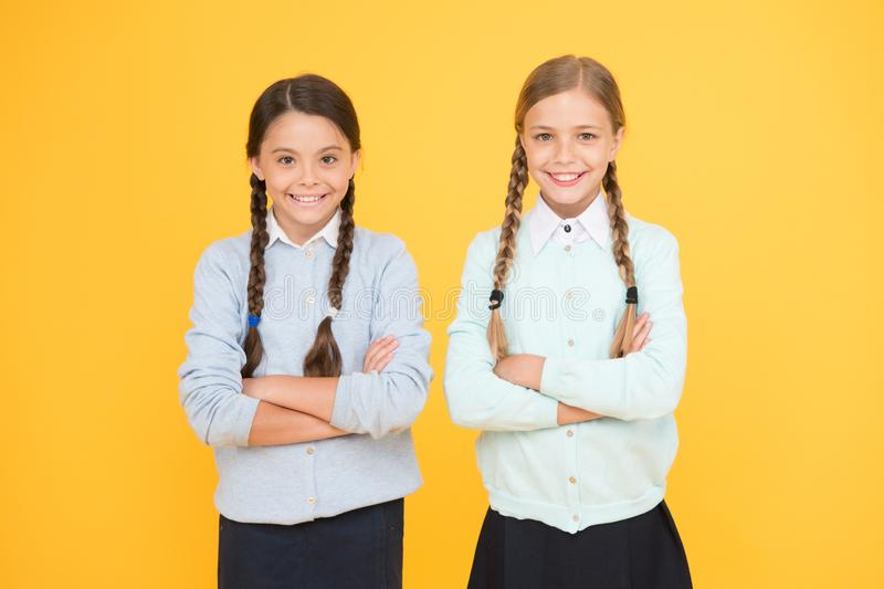 Studying together is fun. smart little girls on yellow background. knowledge day. happy childhood. kid fashion stock image