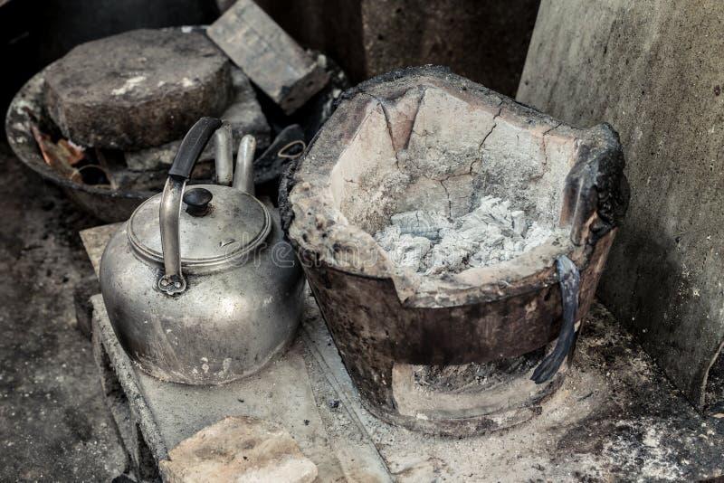 Stufa asiatica di vecchio lerciume con il carbone dell'ustione ed il vaso del bollitore fotografie stock libere da diritti