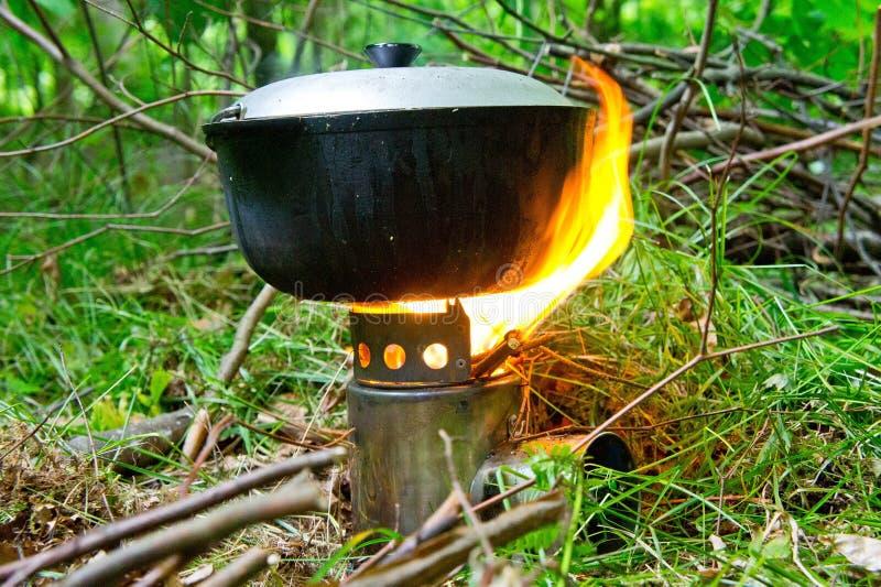Stufa di campeggio con fuoco ed il vaso di alimento pronto contro lo sfondo dei verdi della molla fotografia stock libera da diritti